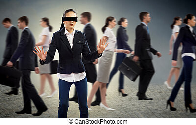 young blindfolded woman seeking a way out in a crowd