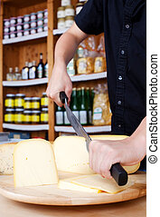 Cutting Cheese - Human hands cutting cheese with knife and...