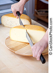 Man slicing cheese - Worker slicing the cheese using double...