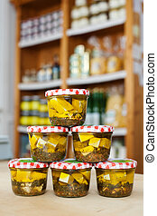 Jars of white cheese cubes and herbs in a grocery - Jars...