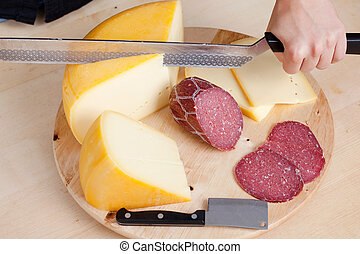 Cheese and wurst slicing with double handed knife on a...