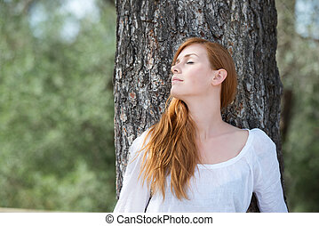 Beautiful woman relaxing in woodland standing leaning...