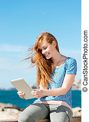 Woman reading an e-book at the sea - Casual happy young...