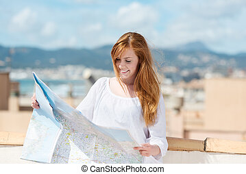 Woman with a route map planning her sightseeing while on...