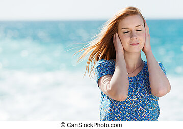 Beautiful woman enjoying the sea breeze standing with her...