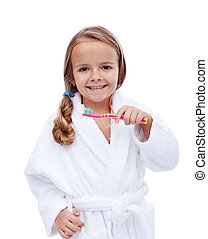 Little girl in bathrobe washing teeth