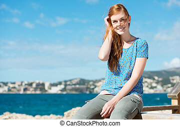 Young woman enjoying life at the sea sitting on a wooden...