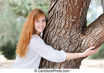 Young woman hugging a tree to show her appreciation and love...