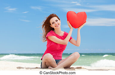 Redhead teen girl with heart shape on the beach