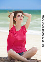 Funny teen girl sitting on the sand at the beach.