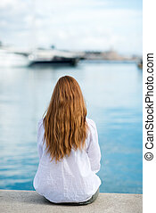 Woman sitting at the harbour on the quay with her back to...