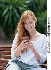 Young woman sending an SMS - Young woman sitting on a wooden...