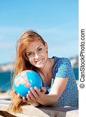 Smiling woman with a globe at the seaside - Conceptual image...