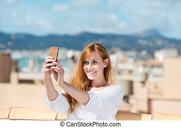 Smiling woman taking her photograph using a mobile phone and...