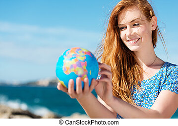 Smiling woman holding a globe at the sea - Smiling beautiful...