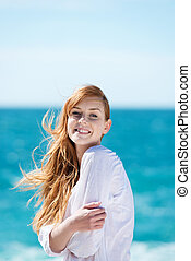 Beautiful young woman at the ocean standing against a...