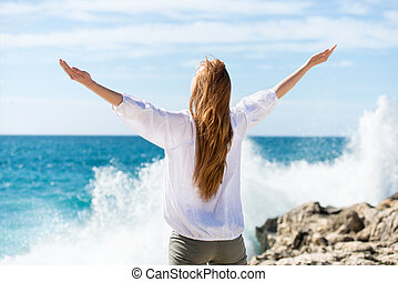 Woman meditating at the sea standing with her arms outspread...