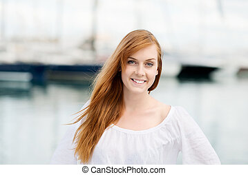 Pretty young woman at the harbour posing in the summer...