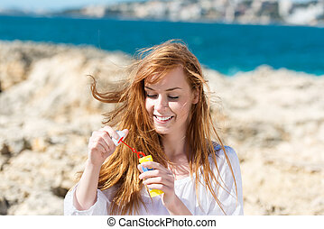 Playful woman blowing soap bubbles standing on a rocky...