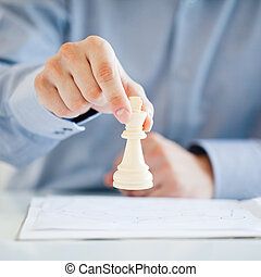 Business Strategy - A man playing chess and thinking about a...