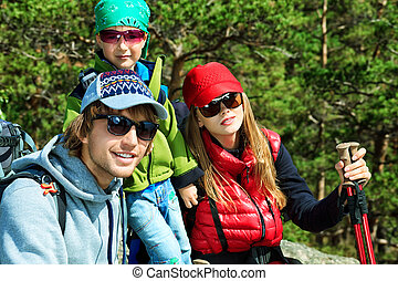 adventure - Happy parents hiking with their little son.