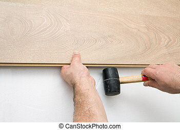 Worker installing laminate floor using a hammer