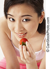 young woman eating strawberry