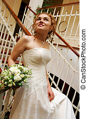 Bride walking downstairs with bouquet