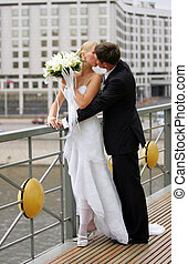 Newlywed couple kissing in urban scene