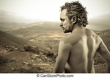 Warrior man covered in mud on desert background