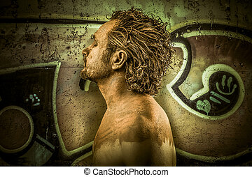 Warrior man covered in mud on grafitti background