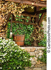 Old water well and a wooden bucket among ivy leaves - Old...