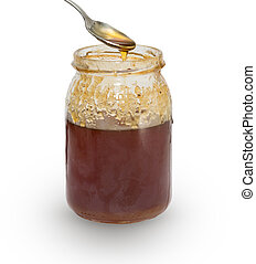 honey - Closeup view of honey over silver spoon and jar,...
