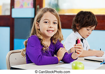 Girl Holding Color Pencils With Friend Drawing In Background