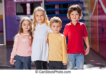 Children Standing Arms Around In Kindergarten - Portrait of...