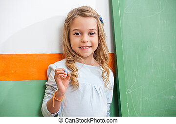 Little Girl Standing By Green Chalkboard In Classroom -...