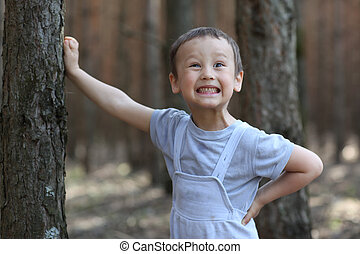 Funny boy 3-4 old at tree in forest