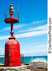 Small red lighthouse on harbor entrance of Imperia in...