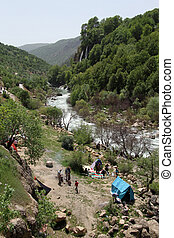 People near waterfall in Bisheh village in Iran