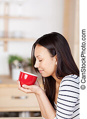 woman enjoying the aroma of coffee at home with closed eyes