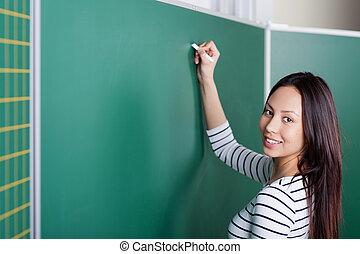 young female teacher writing on blackboard - female teacher...