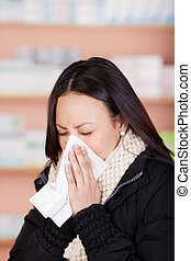 young woman with a cold using paper tissue in pharmacy