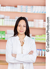 young saleswoman with folded arms in a drug store