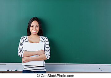 young asian student holding binder and leaning against board