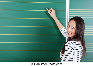 schoolgirl writing on blackboard