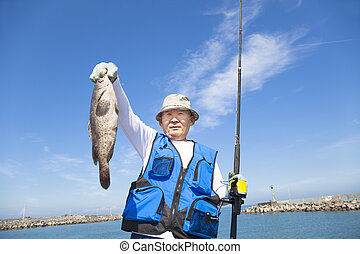 happy senior fisherman showing large grouper