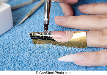 artificial nails - The master puts a brush a material for...