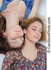 Two beautiful young women girl friends lying head to head &...