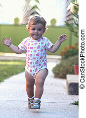 The first independent steps of a baby girl. Natural colors,...