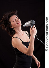 Beautiful woman drying her hair with hairdryer over black...